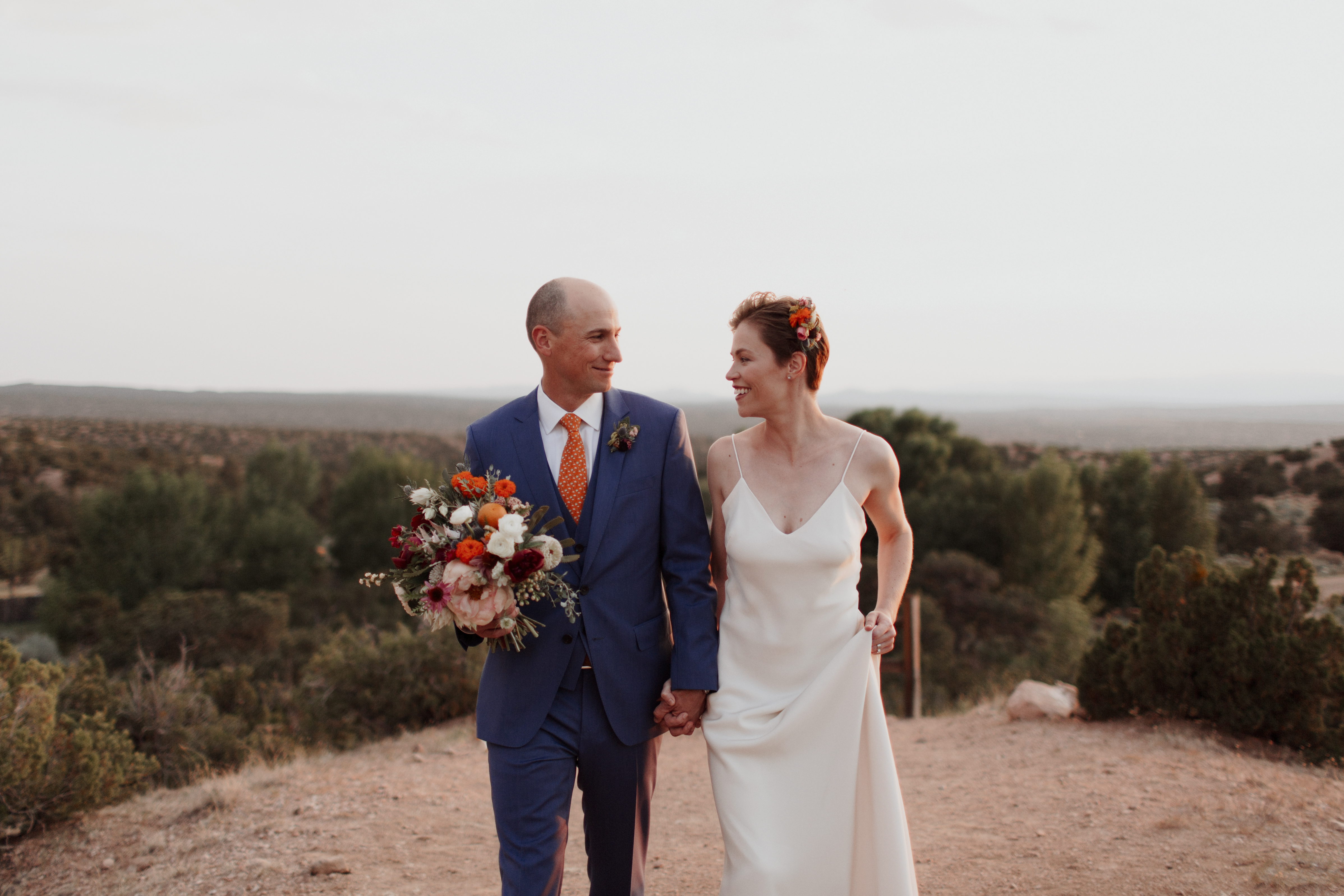 landscape romantic simple updo flowers jewel tones wedding outdoor ceremony planning New Mexico design inspiration orange blue suit silk gown bouquet vows officiants real hair bridal photography romantic couple natural light