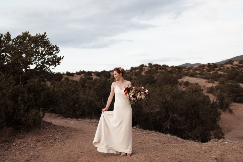 outdoor photography wedding desert landscape planning bouquet jewel tones simple gown bridal updo hair piece silk nature New Mexico photography